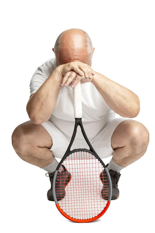 Adult bald man in sportswear with a tennis racket in his hand. Defeat and annoyance. Isolated on a white background. Vertical royalty free stock image