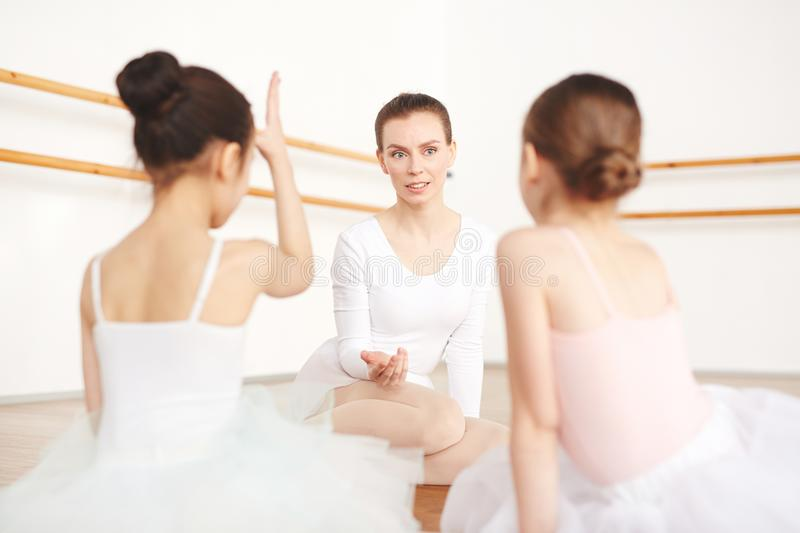 Adult ballerina talking with female students on floor royalty free stock images