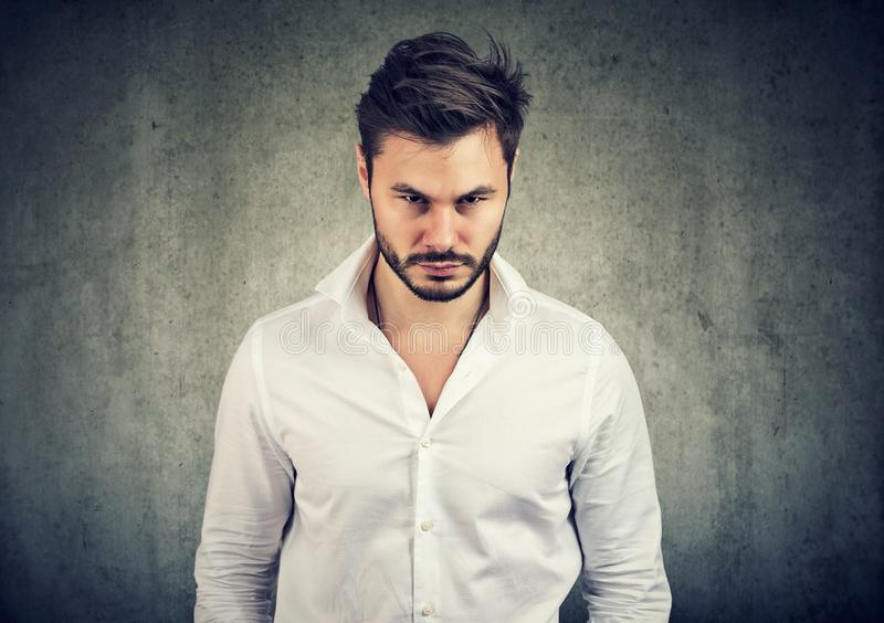Bearded man in white shirt looking with anger and offense at camera on gray background. Adult bearded man in white shirt looking with anger and offense at camera stock photos
