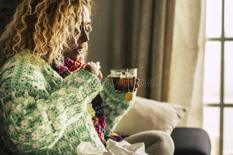 Adult beautiful caucasian woman at home sick with ill and cold drinking  hot tea - fever and seasonal influenza illness concept. For unhealthy people sitting royalty free stock photo