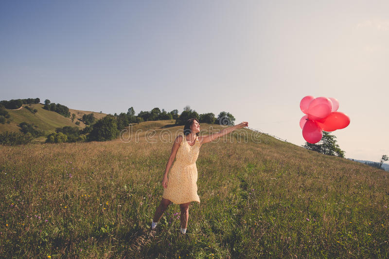 Adult beautiful girl playing with red balloons. On the field royalty free stock photos