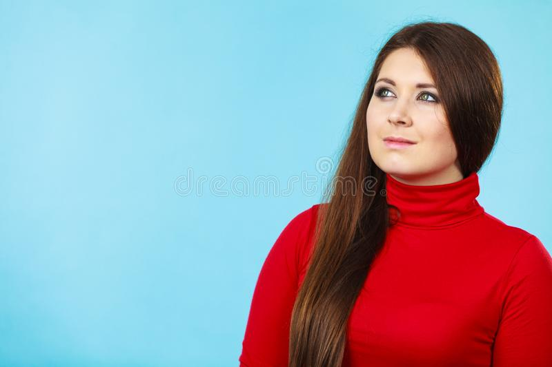 Adult beauty being neutral. Female beauty concept. Closeup portrait of young adult woman having neutral face expression wearing red turtle neck royalty free stock image