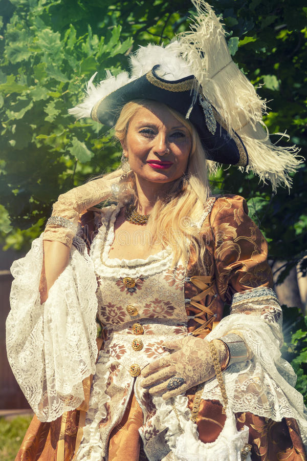 Adult blond woman in Venetian costume. Outdoor royalty free stock image