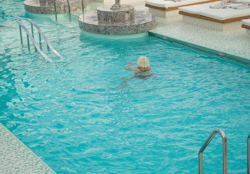 Adult blonde woman enjoys swimming in a luxurious pool on a cruise ship royalty free stock image