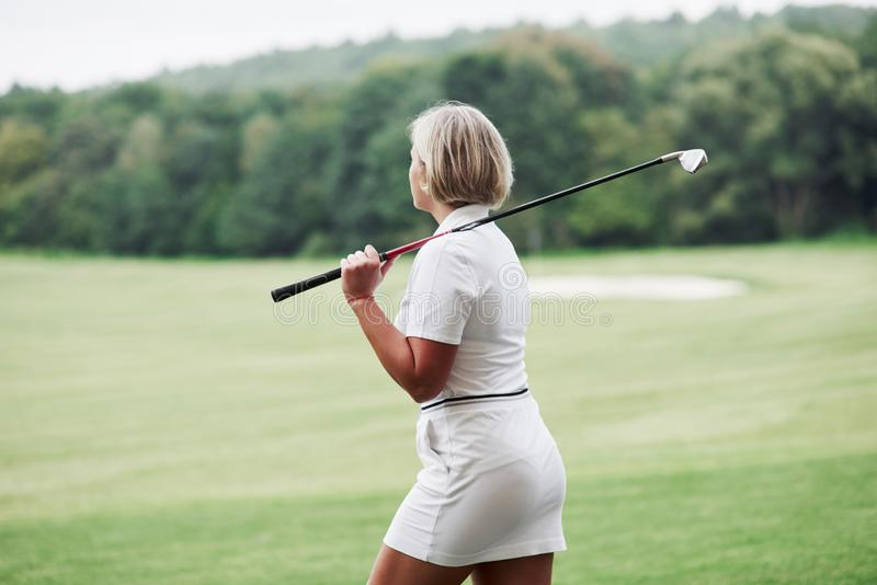 Adult blonde woman have walk on the field while holding the golf stick stock photography