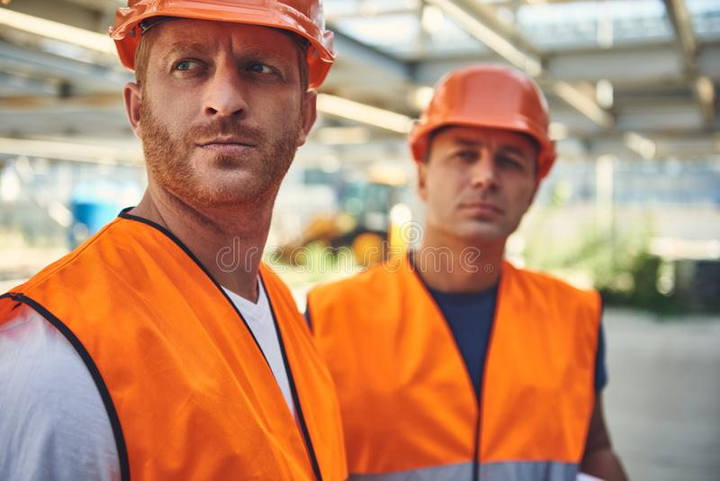 Two mans in helmets are standing on unfinished building stock photo