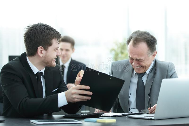 Adult businessman talking with a young colleague in the office stock images