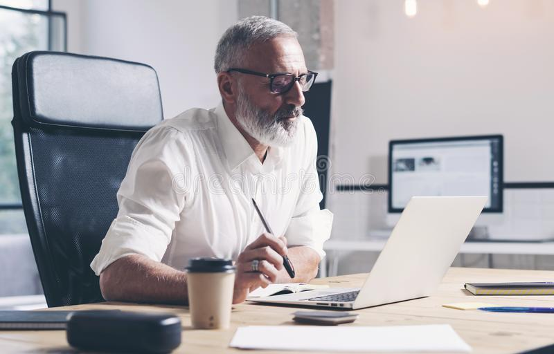 Adult businessman working on mobile laptop computer while sitting at wooden table at modern office place. royalty free stock photos
