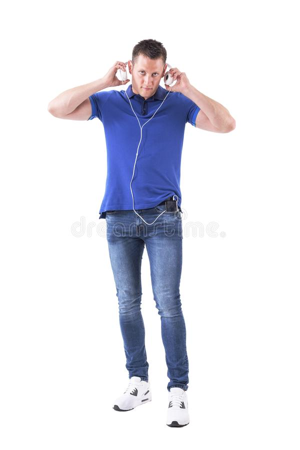 Adult casual male put on headphones connected to cell phone looking at camera. royalty free stock photo