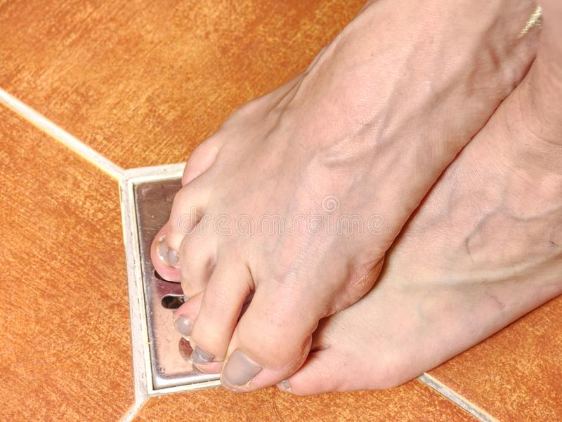 Adult caucasian female foot  in shower. Adult caucasian female foot with short nails   in shower. Feet stay on  tile of modern bathroom young woman white wet royalty free stock photography