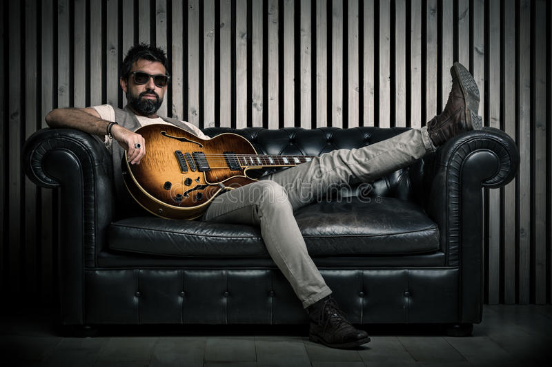 Adult caucasian guitarist portrait with electric guitar sitting on vintage sofa. Music singer concept on couch and. Modern wood wall royalty free stock image