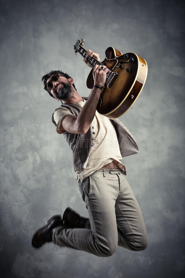 Adult caucasian guitarist portrait playing electric guitar and jumping on grunge background. Music singer modern concept royalty free stock images