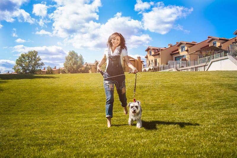 Adult Caucasian happy woman run in the park with her beloved dog Schnauzer. fun mood. concept of love for animals. best friends. Adult Caucasian happy woman run royalty free stock photos