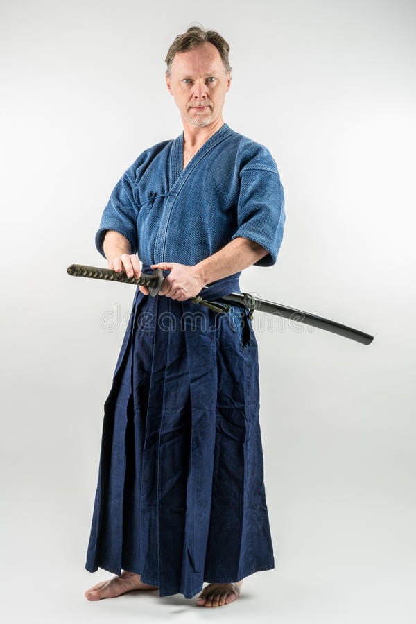 Adult caucasian male training Iaido about to draw a Japanese sword with focused look. stock photo