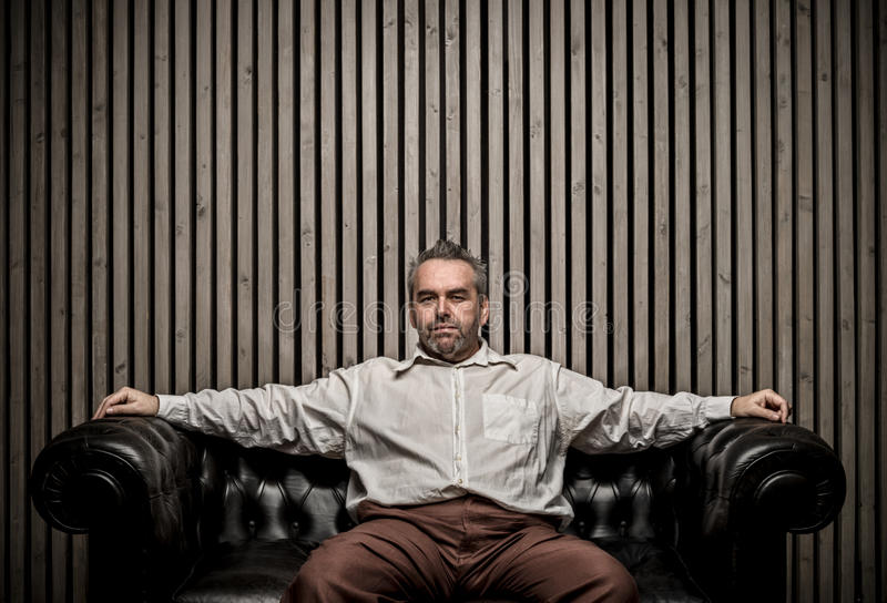 Adult caucasian man sitting on vintage sofa portrait. Writing copy space and wood wall, middle age, shirt stock image