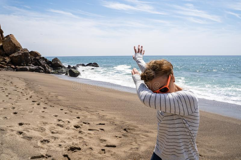 Adult caucasion woman does a dabbing dance move while on the beach. Taken at Point Dume Malibu California.  royalty free stock photos