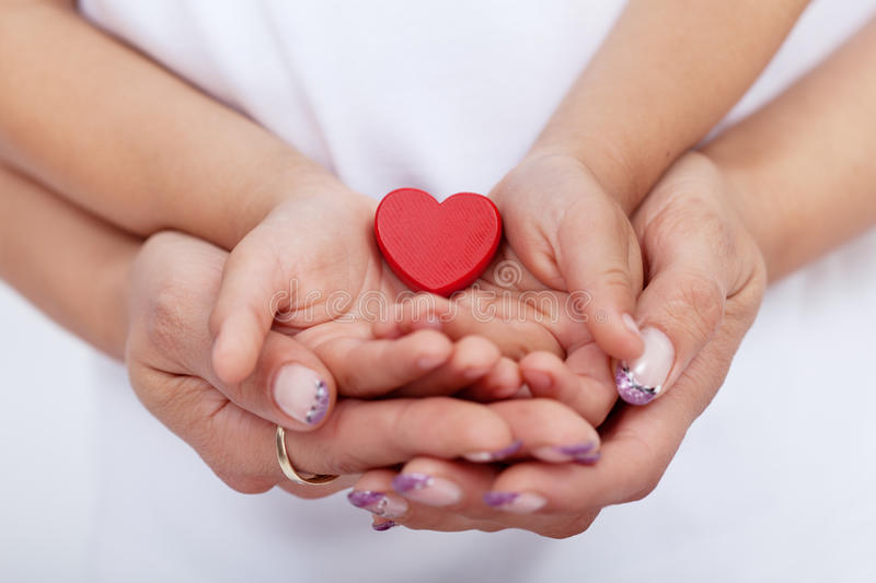 Adult and child hands holding red heart. Together-shallow depth of field royalty free stock photo