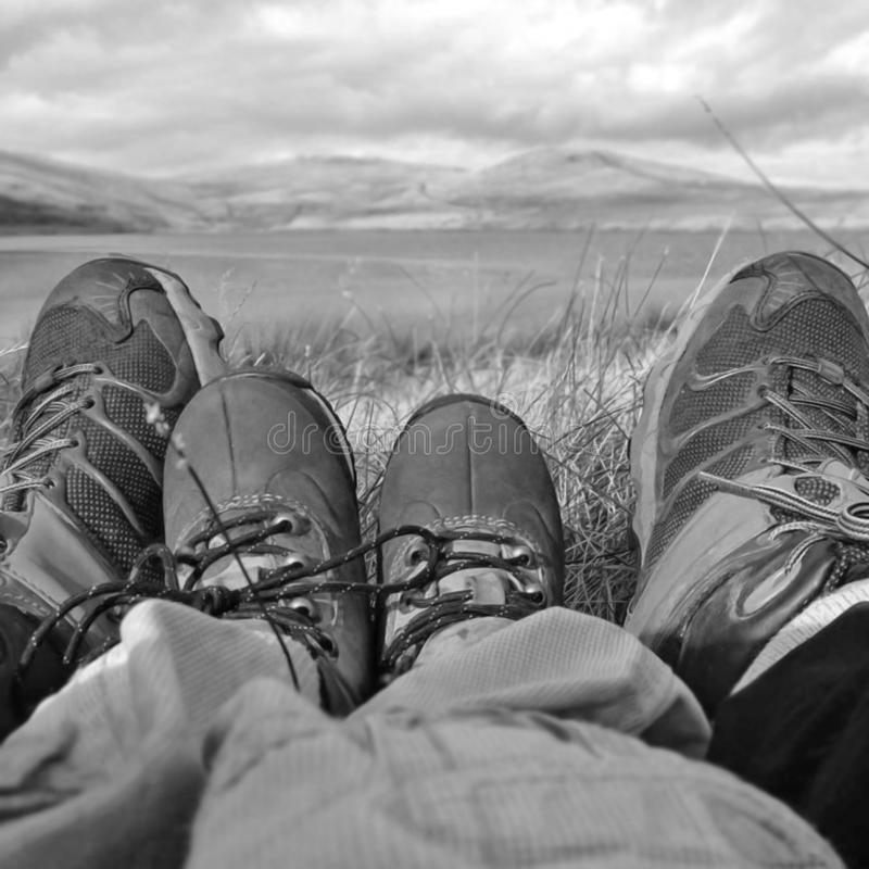 Adult and child legs and feet. Towards mountains and hills royalty free stock image