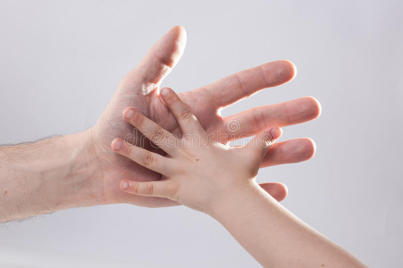 Adult and child's hand touching help tenderness. Adult reaching out to child royalty free stock image