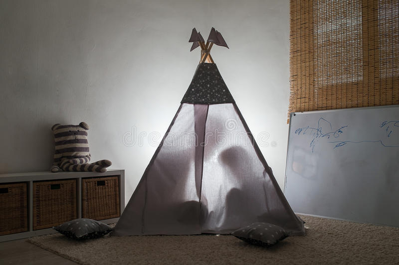 Adult and child sitting in a teepee in the nursery. The glow from the children`s tent. The outline of two people royalty free stock photos