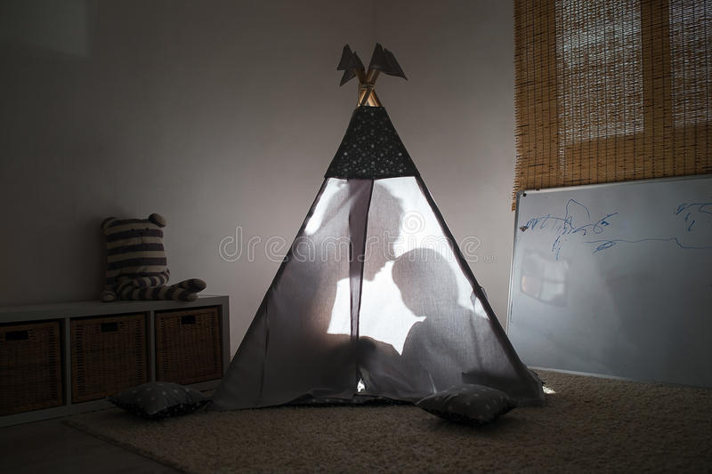 Adult and child sitting in a teepee in the nursery. The glow from the children`s tent. The outline of two people stock image