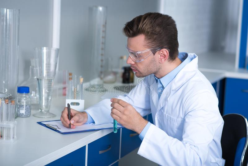 Adult clever scientist sitting and noticing results of research. Researching results. Adult clever handsome discoverer sitting on the chair in the laboratory royalty free stock photo