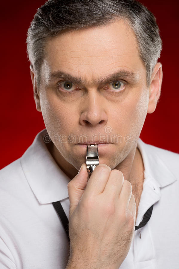 Adult coach man blowing into whistle. royalty free stock images