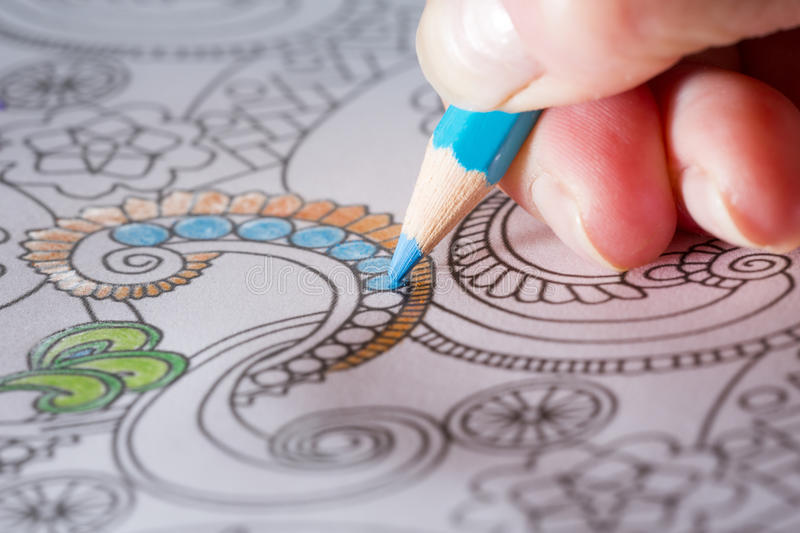 Adult coloring book and colorful pencils. An image of a new trendy thing called adults coloring book. The idea is that a person is coloring an illustrative and stock photos