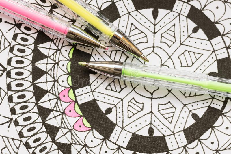 Adult coloring book, new stress relieving trend. Art therapy, mental health, creativity and mindfulness concept. Adult coloring page with pastel colored gel stock photography