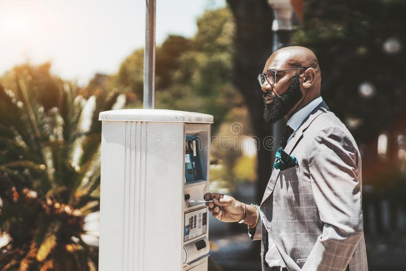 Black guy, parking payment terminal stock photography