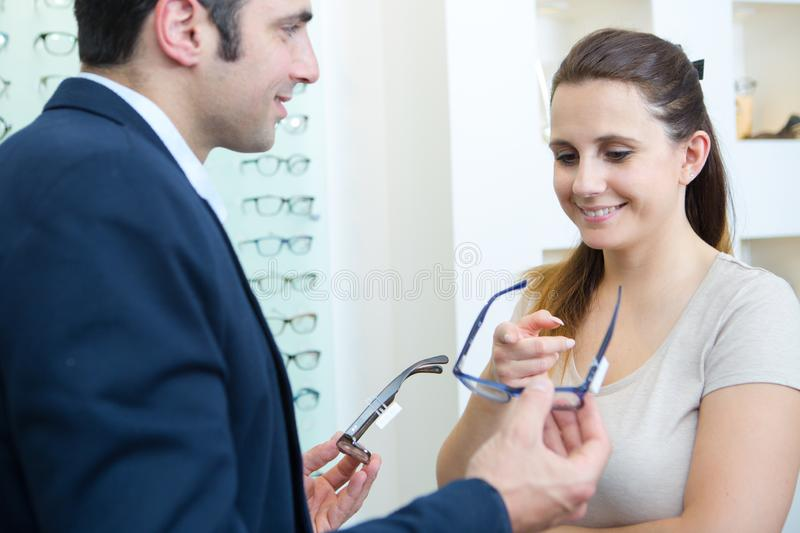 Adult consultant and male customer choosing glasses in optics store royalty free stock photo