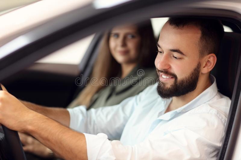 Adult couple choosing new car in showroom. Picture of adult couple choosing new car in showroom royalty free stock images