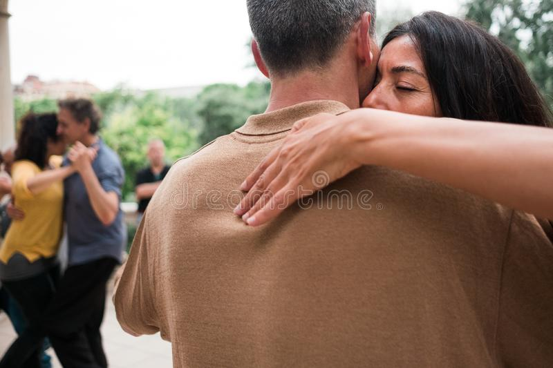 Barcelona, Spain - 10 july 2019: adult couple dancing tango with passion and huggin tight in outdoors park moving close to each royalty free stock photography