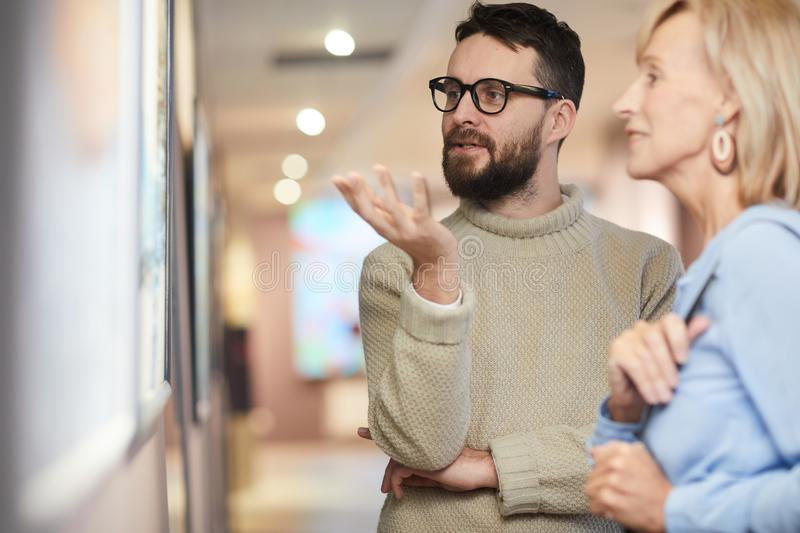 Adult Couple Discussing Painting in Art Gallery stock image