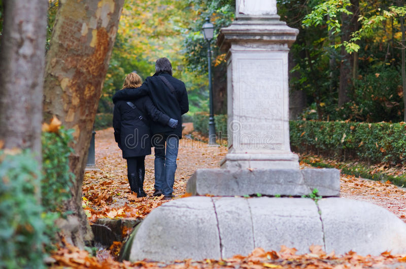 Adult couple in love walking in a park royalty free stock image