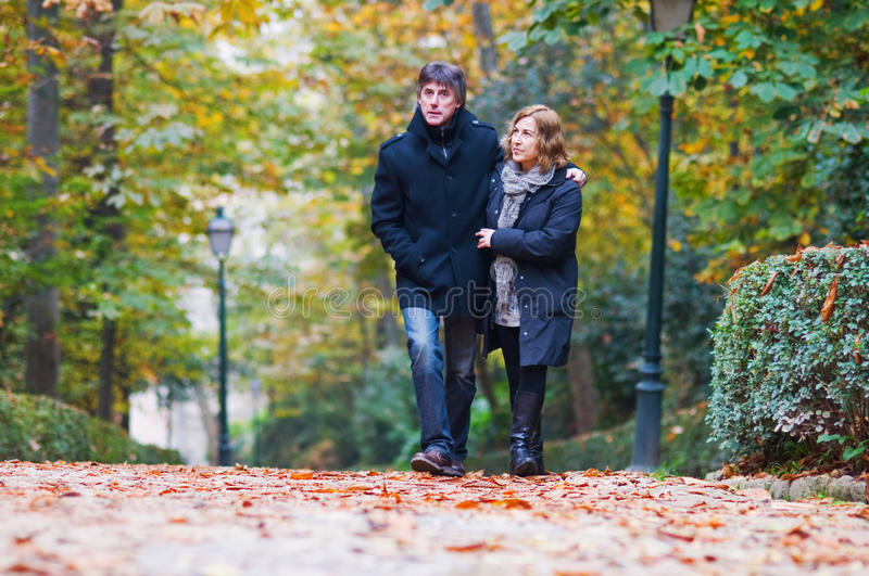 Adult couple in love walking in a park royalty free stock images
