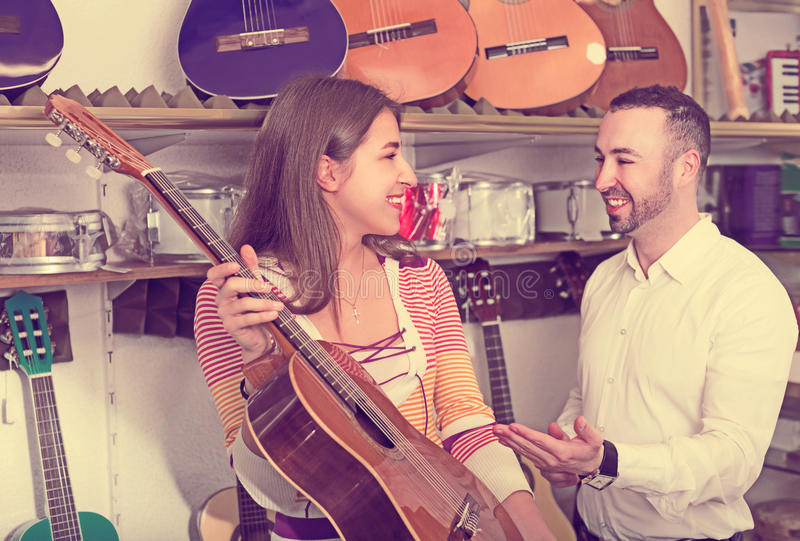 Adult couple selecting acoustic guitar in shop. Adult couple selecting acoustic guitar in music instruments shop stock images