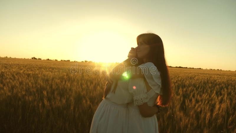 Adult daughter in arms of her mother in a field in the rays of the sun. mom strokes her daughter`s hair. Mom gently hugs. Adult daughter in arms of her mother in stock photography