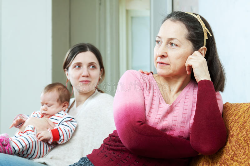 Adult daughter with baby asks for forgiveness from mother. Adult daughter with baby asks for forgiveness from her mother. Focus on mature woman royalty free stock image