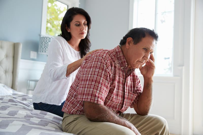 Adult Daughter Comforting Father Suffering With Dementia stock photography