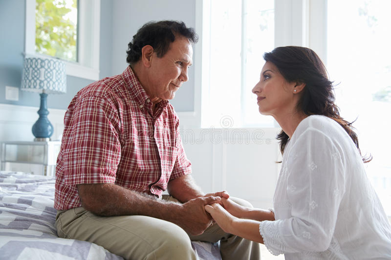 Adult Daughter Comforting Father Suffering With Dementia stock photo