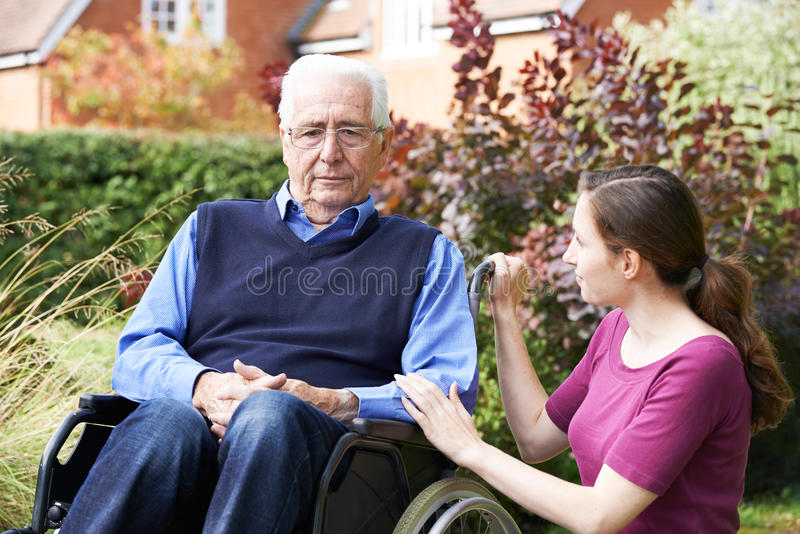 Adult Daughter Comforting Senior Father In Wheelchair. Adult Daughter Comforts Senior Father In Wheelchair stock image