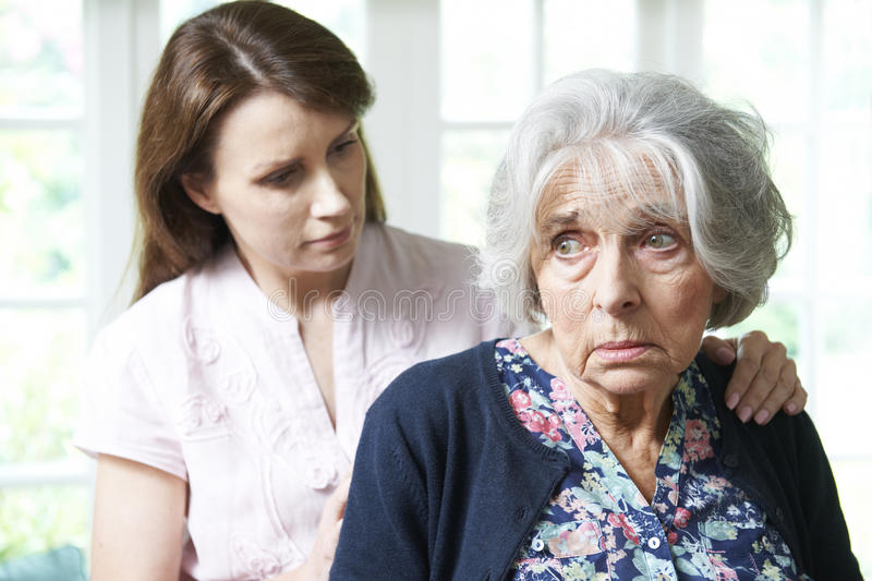 Adult Daughter Consoling Senior Mother At Home. Adult Daughter Consoling Worried Senior Mother At Home royalty free stock photos