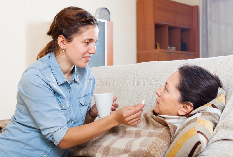 Adult daughter giving pills to mature woman stock image