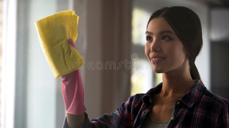 Adult daughter helping mother in general cleaning, washing windows, house chores royalty free stock photo