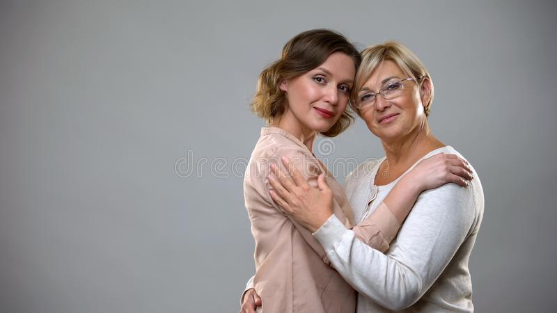 Adult daughter and mother hugging looking in camera, tender family relations royalty free stock photos