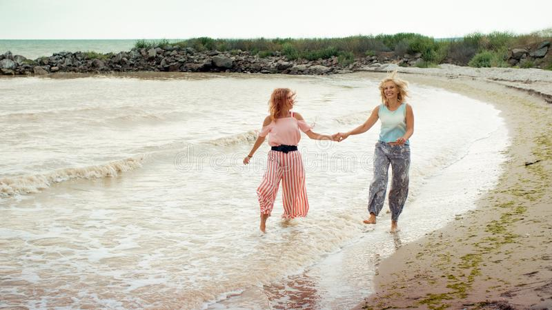 Adult daughter and mother walking on the sea shore holding hands royalty free stock images