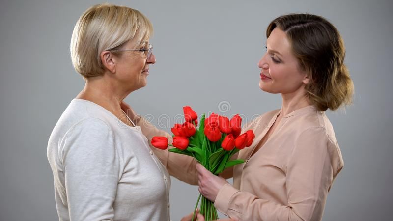 Adult daughter presenting senior mom tulips and hugging, love and care relations stock photography