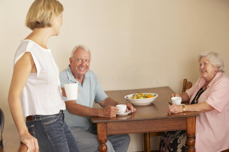 Adult Daughter Sharing Cup Of Tea With Senior Parents In Kitchen stock images