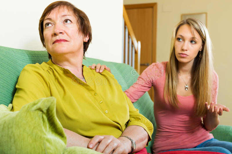 Adult daughter tries reconcile with mother. In home. Focus on mature stock photos